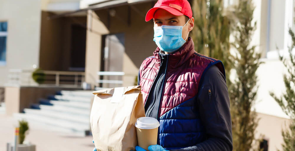 Food delivery person with mask and gloves. Many restaurants switched to delivery services during Covid-19 shutdowns, causing insurance worries.